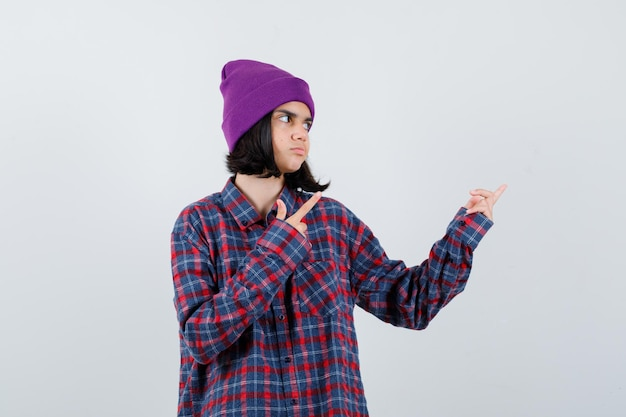 Женщина-подросток в клетчатой рубашке и фиолетовой шапке, указывающая вправо, сосредоточена