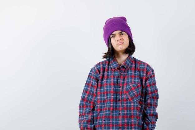 체크 무늬 셔츠와 비니를 입은 십대 여성이 불만족스러워 보이는 입술을 구부리고 있습니다.