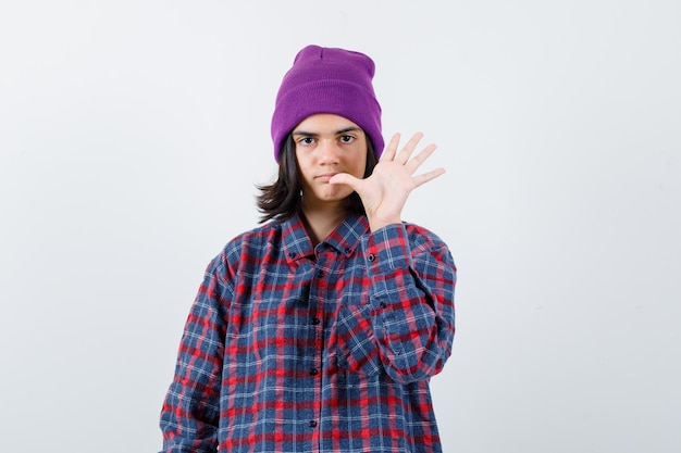 市松模様のシャツとビーニージェスチャーで孤立した10代の女性