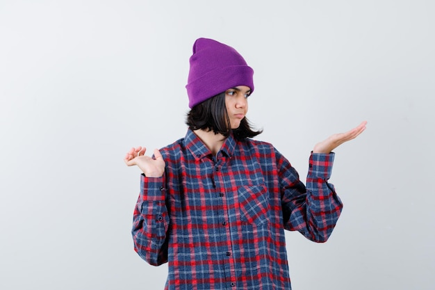 Девушка в клетчатой рубашке и шапочке делает вид, что показывает что-то нерешительное
