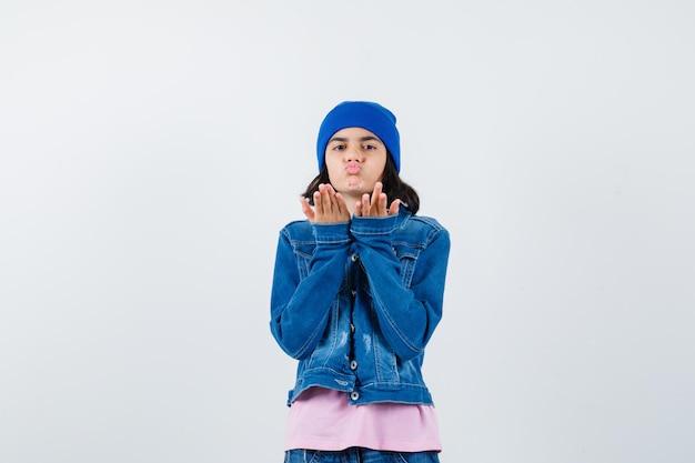 분홍색 t-셔츠 진 재킷과 비니 부는 공기 키스에 십 대 여자