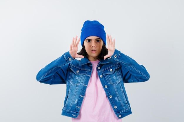 분홍색 티셔츠 진 재킷과 비니를 입은 10대 여성이 놀란 표정을 짓고 있다