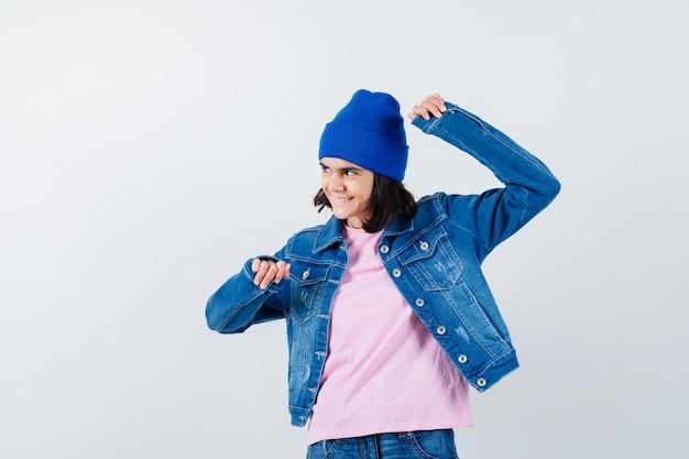 분홍색 티셔츠 진 재킷과 비니를 입은 10대 여성이 승자 제스처를 보여줍니다.