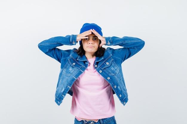 Девушка-подросток в розовой футболке, джинсовой куртке, шапочке, смотрит вдаль с рукой над головой