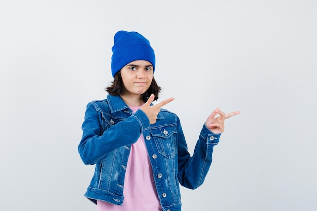 집게 손가락으로 오른쪽을 가리키는 분홍색 티셔츠 진 재킷 비니를 입은 10대 여성