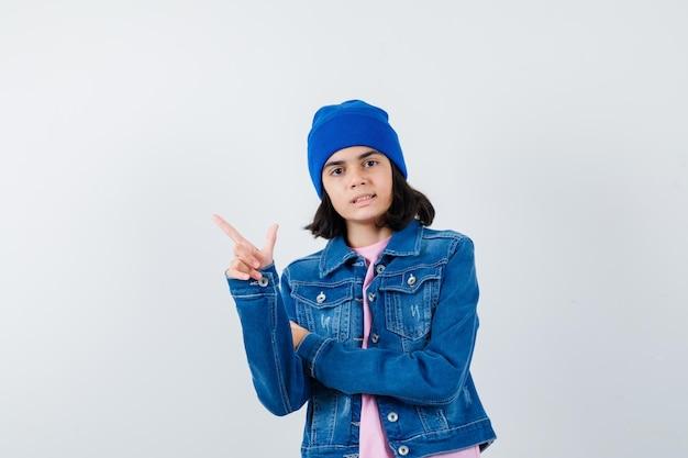 Подросток женщина в розовой футболке джинсовой куртке шапочка показывает жест пальца пистолета, выглядящий мило