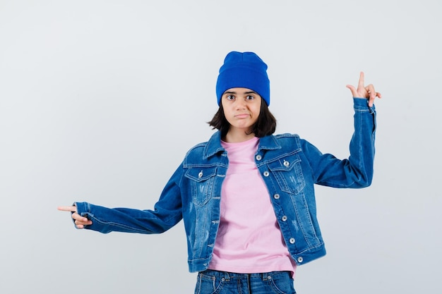 분홍색 티셔츠를 입은 10대 여성이 위를 가리키고 검지 손가락이 진지한 표정으로 왼쪽을 가리키고 있습니다.