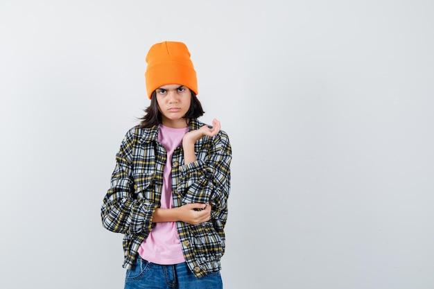 真剣に見える手を上げながらtシャツを着た10代の女性