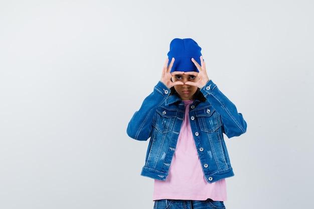 Подросток женщина смотрит сквозь пальцы в розовой футболке, джинсовой куртке, шапочке, выглядит серьезно