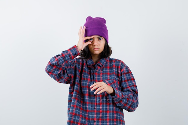 Teen woman opening eye with fingers in checkered shirt and beanie