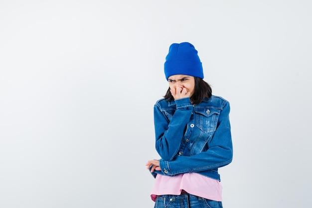 Teen donna in t-shirt rosa giacca di jeans e berretto che morde il pugno che sembra ansiosa