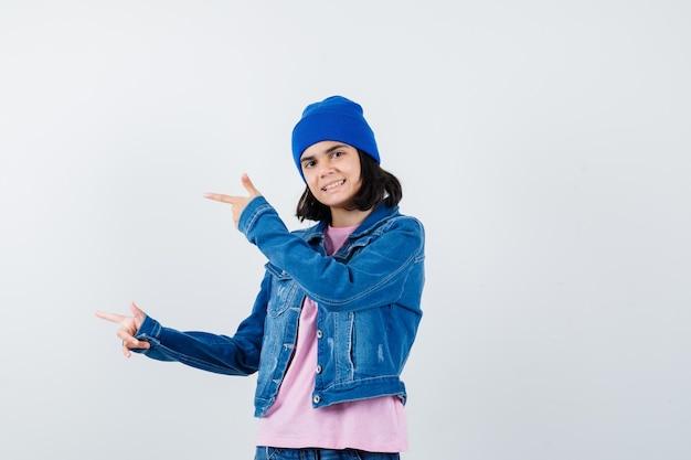 분홍 티셔츠 진 재킷에 검지 손가락으로 왼쪽을 가리키는 10대 여성이 쾌활해 보인다