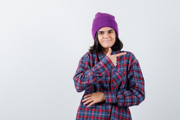 チェックのシャツと陽気な探しているビーニーの人差し指で右を指している10代の女性