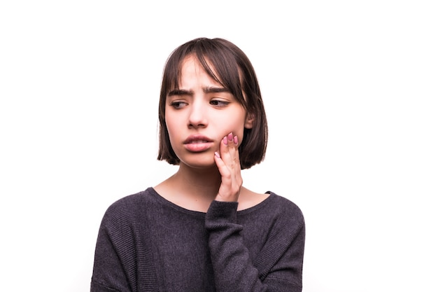 10代の女性が傷ついた頬を、彼女がひどい歯の痛みを持っているかのように痛みを伴う表情で押す。