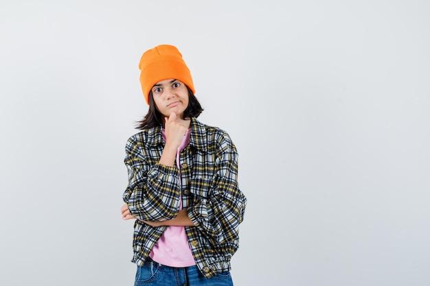 Donna teenager che puntella il mento a portata di mano in berretto giacca t-shirt che sembra pensierosa