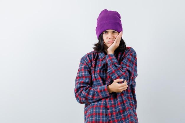 Donna teenager che puntella il mento sul berretto di palma che sembra annoiata