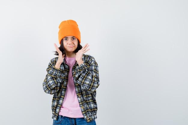 흥분 찾고 t-셔츠 재킷 비니에 얼굴 근처에 손을 올리는 십 대 여자