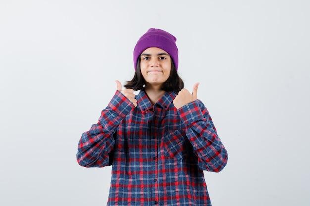 チェックのシャツと陽気な探している紫色のビーニーで二重の親指を示す10代の女性