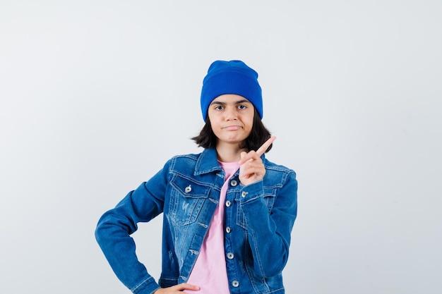 かわいく見えるピンクのtシャツで腰に手をつないで警告ジェスチャーを示す10代の女性