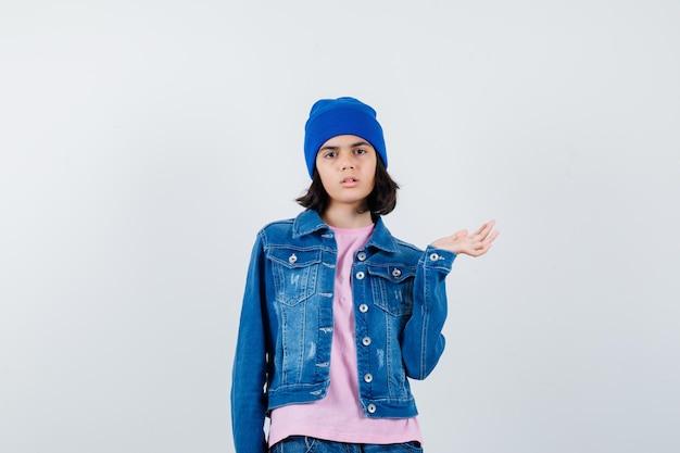 진지해 보이는 분홍색 티셔츠 진 재킷 비니를 입고 손바닥을 옆으로 펼치는 10대 여성