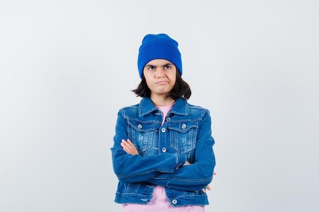 心配そうに見えるピンクのtシャツジーンズジャケットビーニーで腕を組んで立っている10代の女性