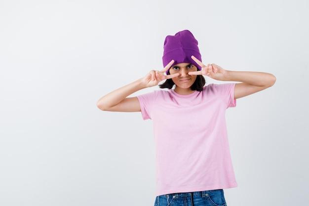 Donna teenager in berretto della maglietta che mostra gesto di vittoria