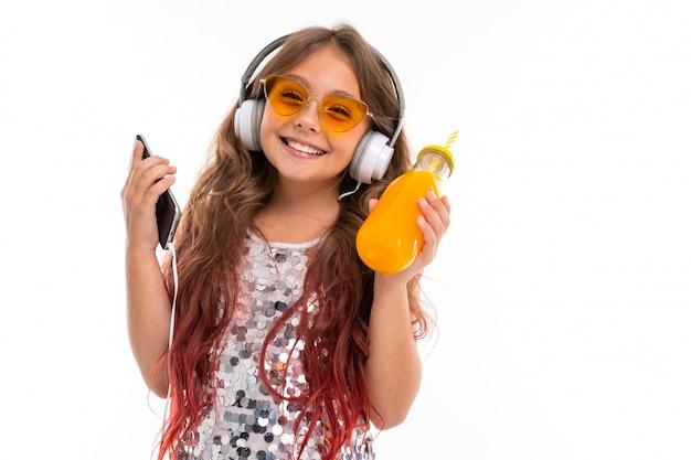 Подростковая женщина с длинными светлыми волосами, окрашенными в розовые кончики, в блестящем светлом платье, черно-белых кроссовках, стоит с наушниками, держит телефон и сок в стеклянной бутылке с полосатой трубкой в руке