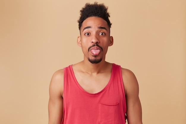 Adolescente afroamericano, uomo dall'aspetto divertente con barba e acconciatura afro. indossare canottiera rossa. mostrando lingua, umore giocoso sul muro beige pastello
