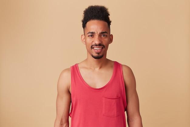 Ragazzo afroamericano adolescente, uomo dall'aspetto scontento con barba e acconciatura afro. indossare canottiera rossa. aggrotta le sopracciglia, infelice isolata sopra la parete beige pastello