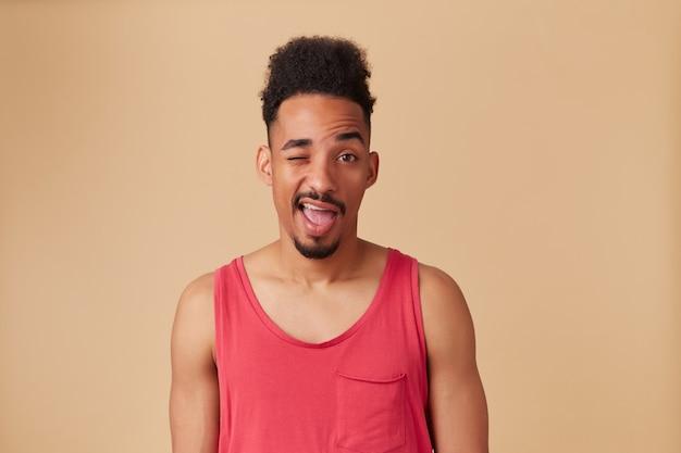 Adolescente afroamericano, uomo dall'aspetto felice con barba e acconciatura afro. indossare canottiera rossa. ampiamente sorriso.