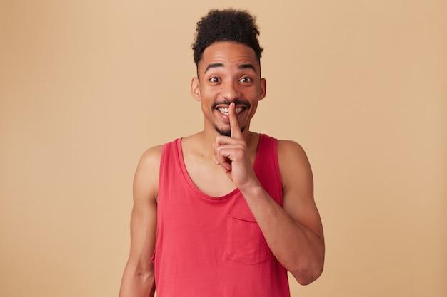 Adolescente afroamericano, uomo dall'aspetto felice con barba e acconciatura afro. indossare canottiera rossa. mostrando il segno di silenzio. tienilo segreto sul muro beige pastello