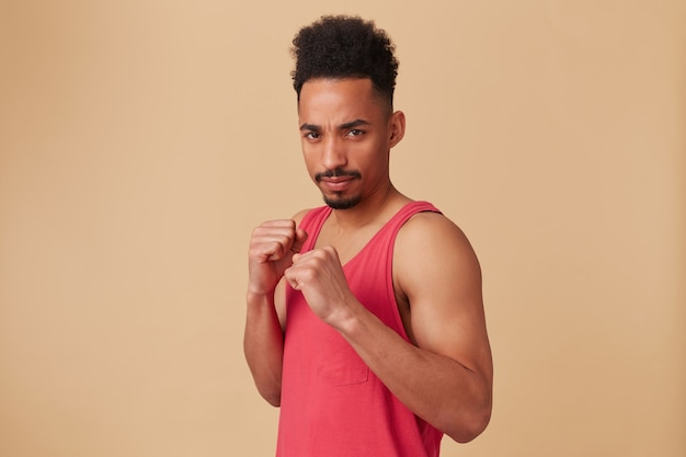 Adolescente afroamericano, uomo dall'aspetto serio con barba e capelli afro. indossare canottiera rossa. stringi i pugni, mettiti in posizione offensiva sul muro beige pastello