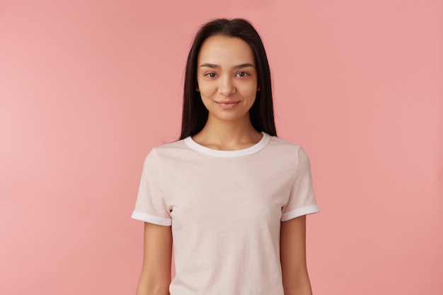 Teenage asian girl, confident looking woman with dark long hair. wearing white t-shirt. people and emotion concept. watching and smiling  isolated over pastel pink wall