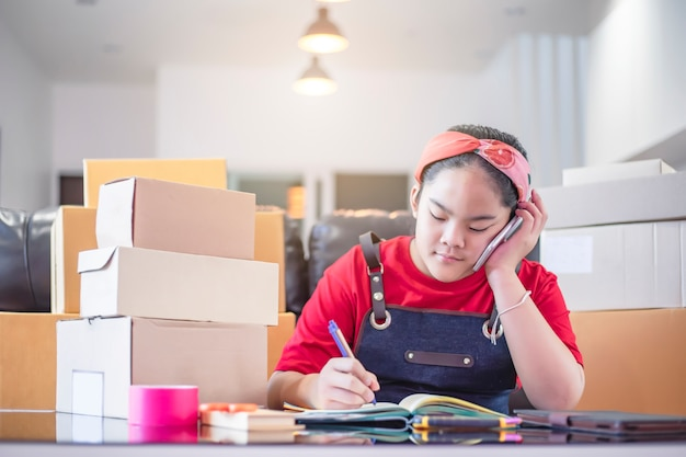 Teenage asian girl prepare delivery boxes at home for online maketing sales. young entrepreneur or freelance girl start up small business with selling something online.