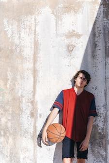 晴れた日に壁に傾いている十代のバスケットボール選手