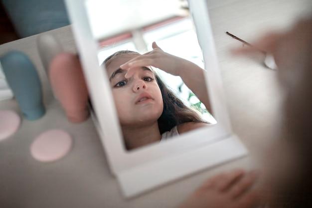 顔の化粧マスクを適用し、ミラー、ウェルネス、リラクゼーションと美容、屋内ライフスタイル、自宅で美容院の前に自宅でスパの手順を行う長い髪の10代の美しい女の子