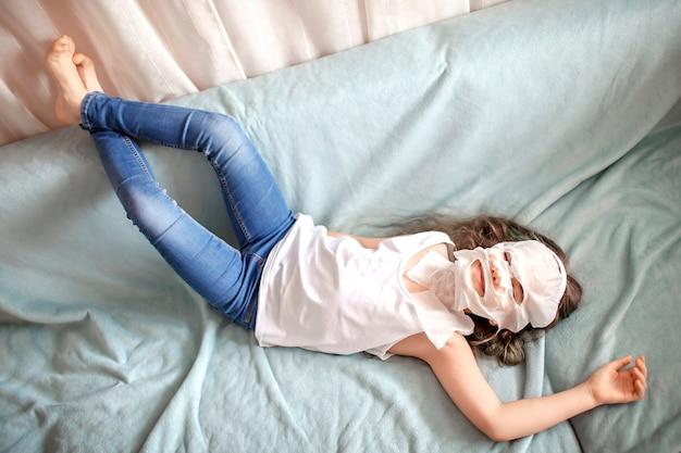 顔の化粧マスクを適用し、自宅でスパの手順を行う長い髪の10代の美しい少女、ウェルネス、リラクゼーションと美容、屋内ライフスタイル、自宅の美容院