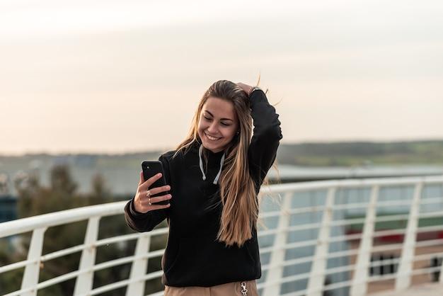 흰색 도시 다리를 걷는 동안 그녀의 휴대 전화로 사진을 찍는 십 대 금발 소녀.