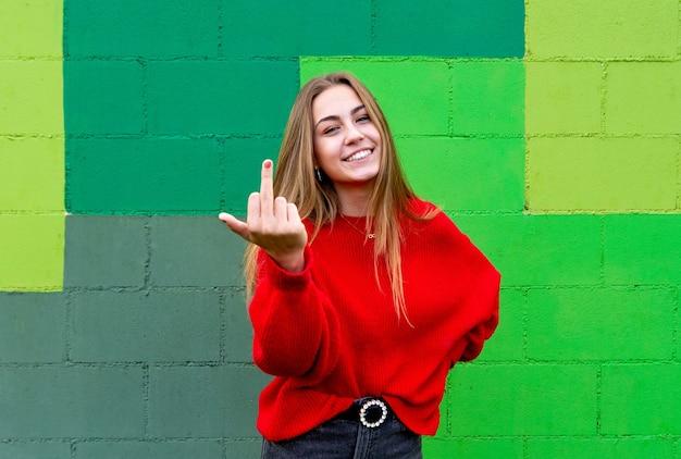 빨간 스웨터와 십 대 금발 여자입니다. 그녀의 가운데 손가락을 보여주는