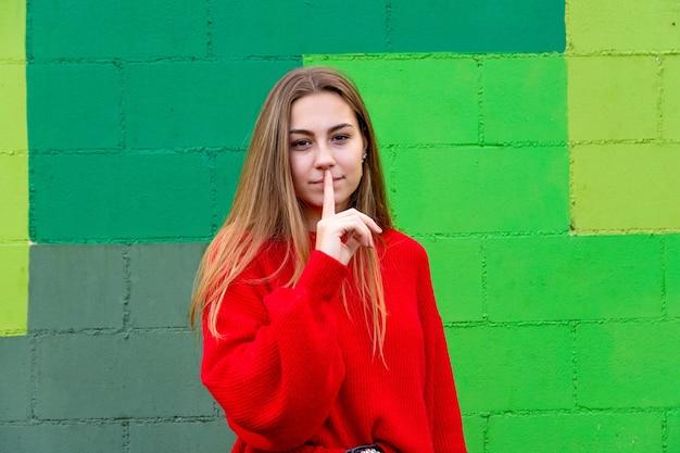 빨간 스웨터와 십 대 금발 여자입니다. 닥쳐.