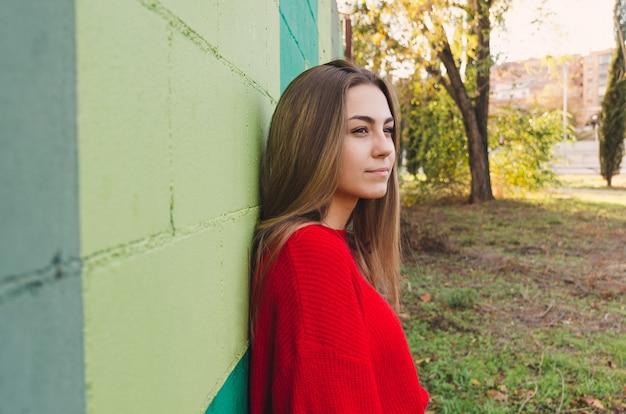 빨간 스웨터와 십 대 금발 여자입니다. 사려 깊은.