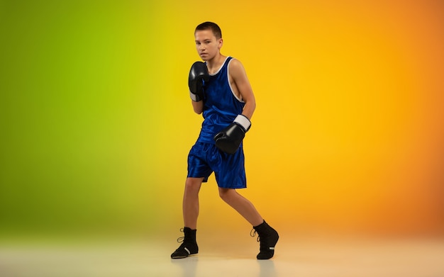 Teenage boxer against gradient neon in motion of kicking, boxing