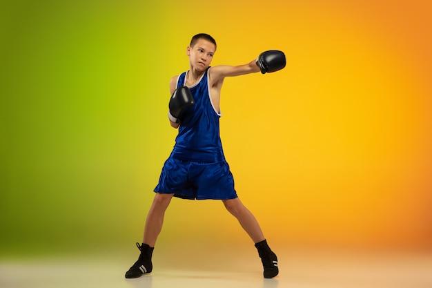 Подростковый боксер на фоне градиентной неоновой студии в движении ногами, боксом
