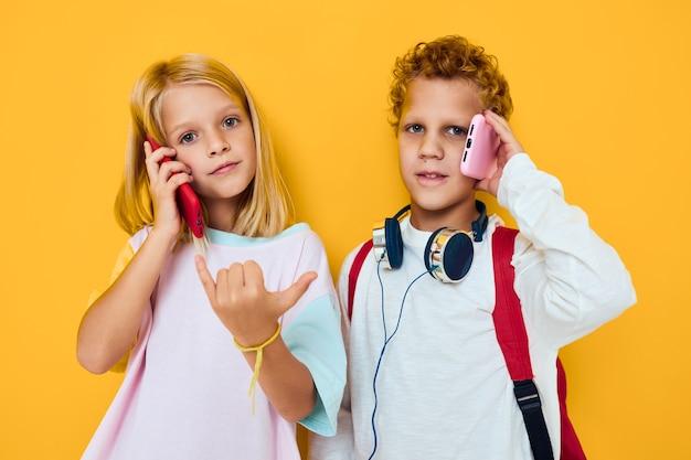 10代の少年と少女は、ヘッドフォンで隔離された背景のガジェットを使用します