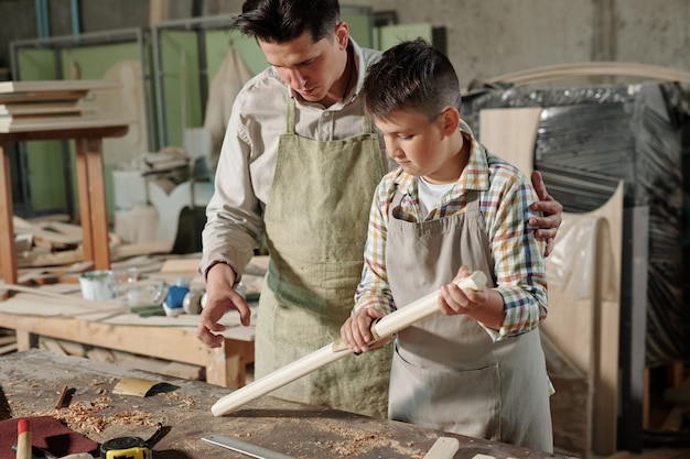 Teenage boy in apron making plank smooth with sandpaper under control of father in carpentry workshop