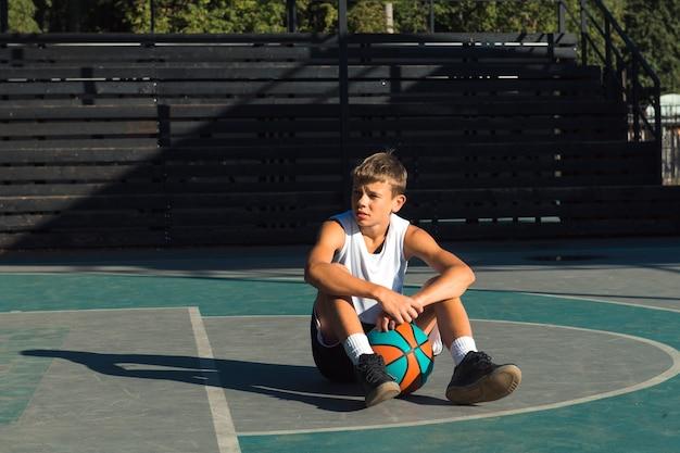 スポーツグラウンドでボールと一緒に座っている10代の少年バスケットボール選手