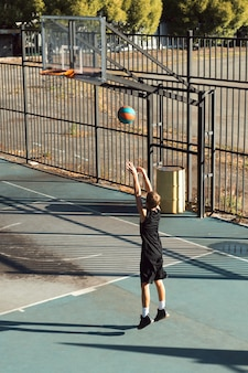 ボールを投げるスポーツグラウンドで一人でトレーニングする10代の少年バスケットボール選手