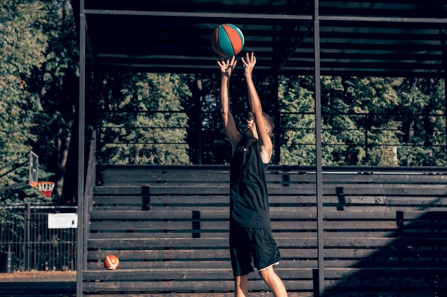Teenage boy basketball player training alone at sports ground throwing ball to hoop