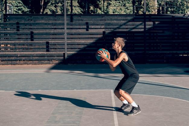 Teenage boy basketball player training alone at sports ground throwing ball