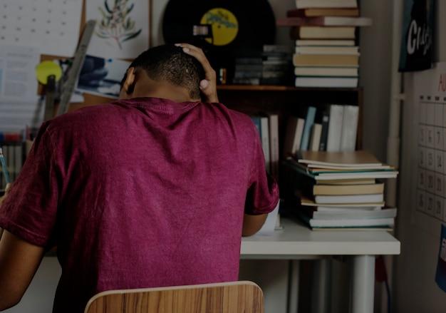 Ragazzo adolescente in una camera da letto che fa lavoro stressato e frustrato